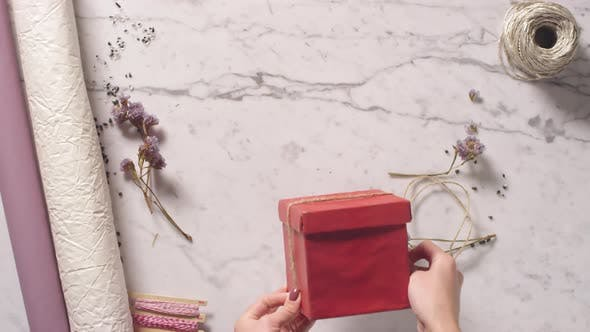 Thumbnail for Female Hands Decorating Red Gift Box with Jute Rope and Tying a Bow