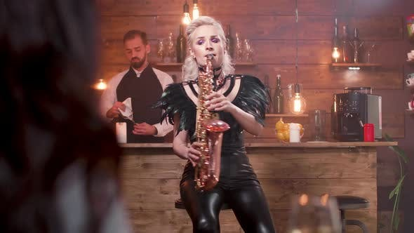 Thumbnail for Female Spectator Raises a Glass of Wine While a Woman Performs a Song on a Saxophone
