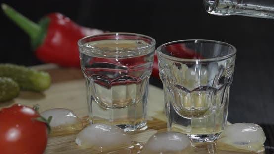Thumbnail for Gießen Sie Wodka aus einer Flasche in Schnapsgläser. Mann nimmt ein Glas mit Wodka