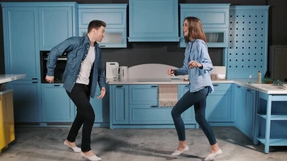 Thumbnail for Happy Family Dance. Young Couple Fun Dancing While Cooking in the Kitchen at Home. Rock and Roll
