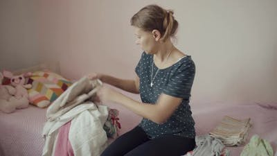 Woman Laying Out Washed Laundry And Clothes
