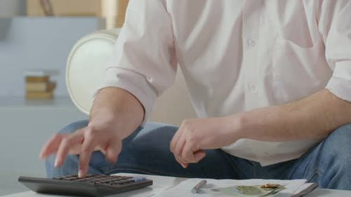 Man Counting Euros, Pressing Buttons on Calculator, Making Notes, Financing