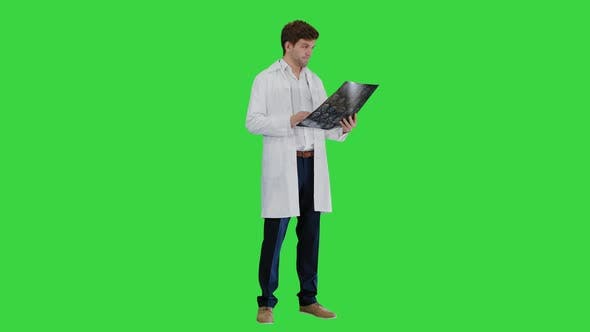Male Doctor Checking Computed Tomography and Looking at Someone Approvingly on a Green Screen