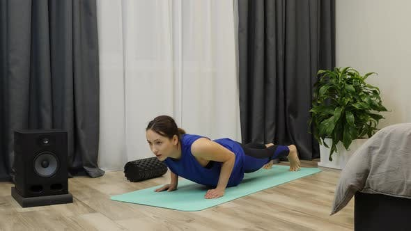 Thumbnail for Woman wearing blue sportswear does push-ups exercises at home. Fitness concept