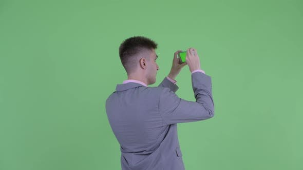 Thumbnail for Rear View of Young Businessman Taking Picture with Phone