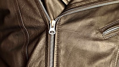 Man Buttoning A Zipper On A Leather Jacket