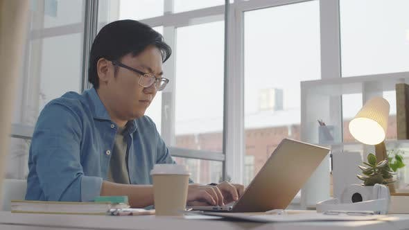 Thumbnail for Frustrated Asian Office Worker Texting on Laptop and Getting Mad