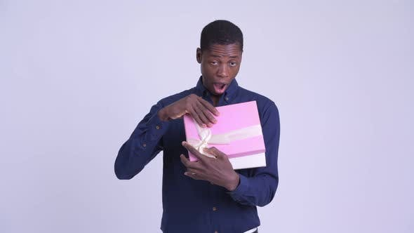 Young Happy African Businessman Opening Gift Box and Looking Surprised