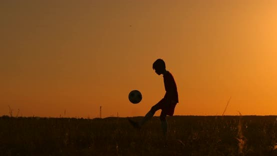 Thumbnail for Silhouette a Boy Juggles a Ball in the Field at Sunset