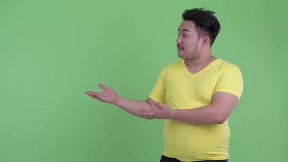 Thumbnail for Happy Young Overweight Asian Man Talking While Showing Something