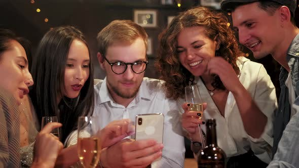 Friends, Men, Women, Leisure, Friendship and Technology Concept - Friends with Smartphones Drinking