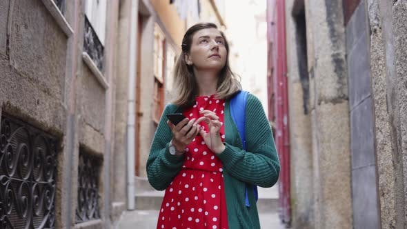 Thumbnail for Young Woman Tourist Is Standing in Old Street, Searching Her Way in Navigator