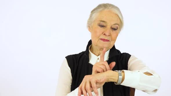 Thumbnail for An Elderly Woman Taps Her Watch, Points Somewhere and Looks at The Camera