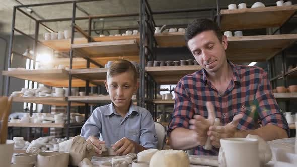 Thumbnail for Attractive Caucasian Man and His Cute Son Having Fun in Pottery