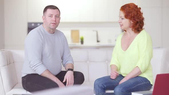 Irritated Adult Caucasian Couple Arguing at Home Sitting on Couch