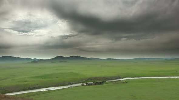 Big River and Gray Storm Clouds on the Vast Meadow in Mongolia