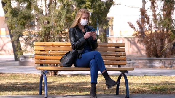 Masked Girl is Texting on the Phone