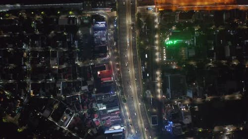 Aerial Top Down View of Vehicles Driving on Multi Lane Highway on a Slight Curve at Night Lit By