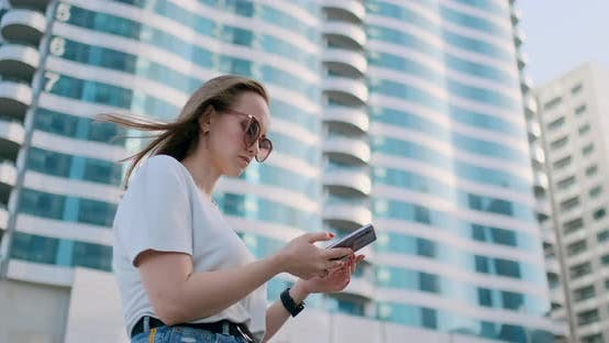 Thumbnail for Tourist Girl in the Summer in Dubai Writes a Message, Looks at a Map on the Smartphone