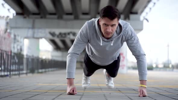 Thumbnail for Sporty guy is doing push ups outdoors in evening in urban city.