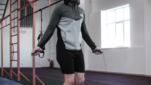 Focused Young Sportsman Training with Skipping Rope in Gym