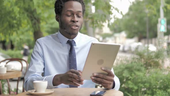 Thumbnail for Online Video Chat on Tablet by African Businessman, Sitting in Outdoor Cafe