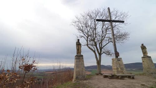 A Historic Sacred Site with Two Statues and a Wooden Cross Set in Nature.