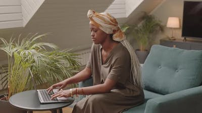 Black Woman Typing on Laptop at Home