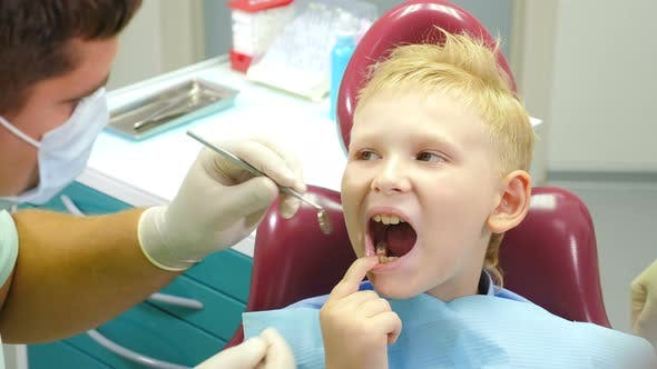 Thumbnail for Dental Health Concept. Male Dentist Treating Little Boy in Dental Clinic. Pediatric Dentistry
