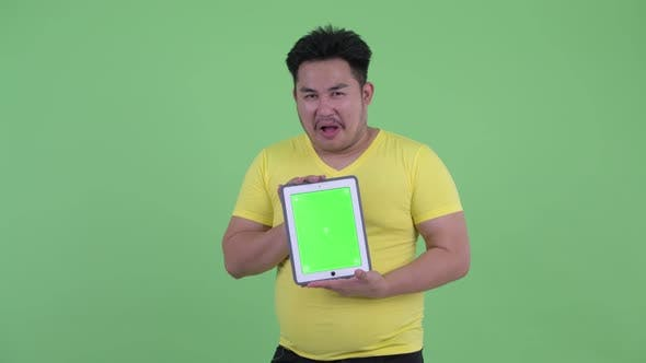 Thumbnail for Happy Young Overweight Asian Man Showing Digital Tablet and Looking Surprised