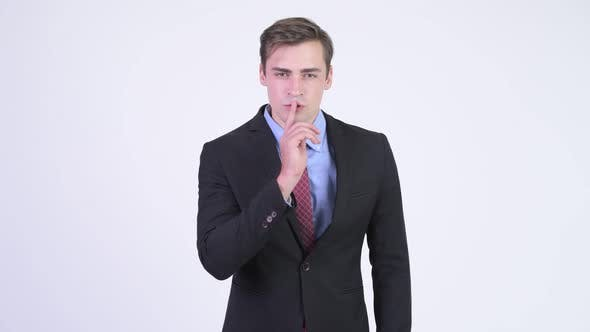 Cover Image for Young Happy Handsome Businessman with Finger on Lips