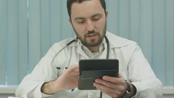 Young  Male Doctor with a Calculator Make Calculations and Make Notes