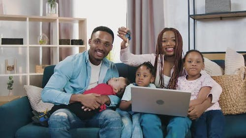 African American Family with Kids Sitting on the Couch in New Own Dwelling and Showing House's Keys