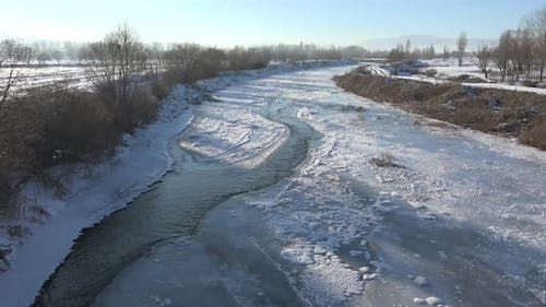 Water Canal Flowing Under Frozen Ice Sheets in Sunny Winter