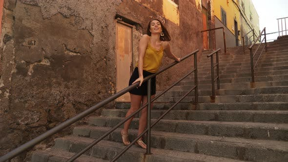 Thumbnail for Brown-Haired Woman Holding on to Stair Railings and Posing on a Windy Day