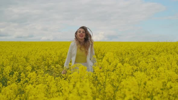 Thumbnail for An Energetic Jumping and Dancing Female Singer with a Microphone in a Field of Rapeseed with Yellow
