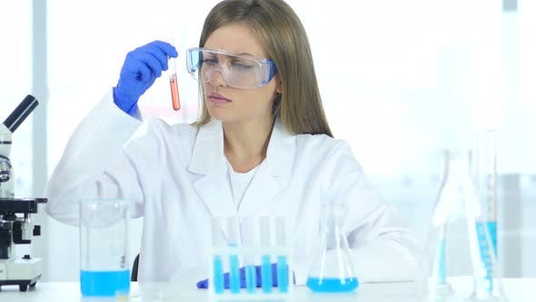 Thumbnail for Female Scientist Looking at Red Solution in Test Tube in Laboratory
