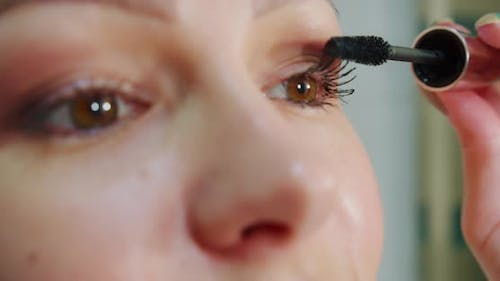 Close Up of Attractive Woman Putting on Makeup with Brush Adding Mascara on Eye