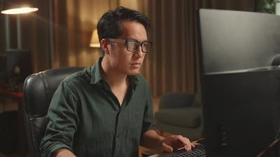 Asian Male Works His Personal Computer. He Works At Night