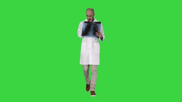 Thumbnail for Doctor Radiologist Looking at X-ray Scan Walking on a Green Screen, Chroma Key
