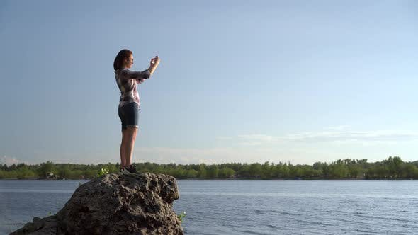 Thumbnail for A Young Woman Stands on a Stone Near the River and Photographs the Landscape. The Girl Takes