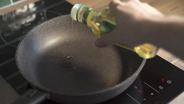 Man Pouring Cooking Oil on the Frying Pan