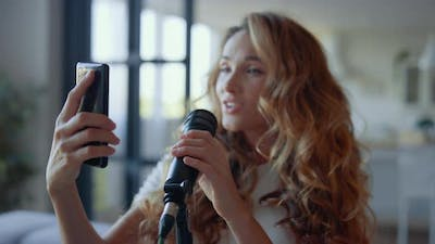 Woman Performing Song in Microphone. Vocalist Looking Text of Song on Smartphone