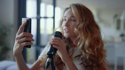 Frau spielt Lied im Mikrofon. Sänger, der Text des Liedes auf dem Smartphone