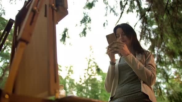 Thumbnail for Art Female Painter Texting in Public Chat in Social Network Near Easel with Canvas