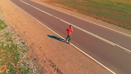 Thumbnail for Low Altitude Flight in Front of Sporty Man at Perfect Asphalt Road