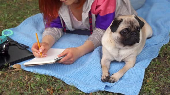 Thumbnail for Girl Laying on a Lawn and Writing Her Pug Laying Beside