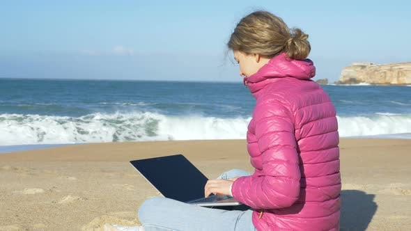 Woman Sits with Laptop on Beach Sand and Works Distantly