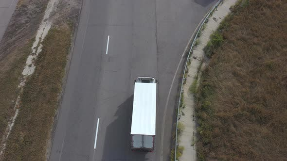 Thumbnail for Aerial View of Truck with White Cargo Trailer Driving on Road To Destination, Flying Over Lorry