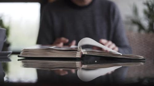 Man Turning Pages Of Photo Album